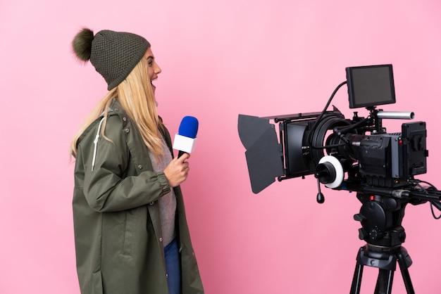 Repórter mulher segurando um microfone e reportando notícias sobre parede rosa rindo na posição lateral