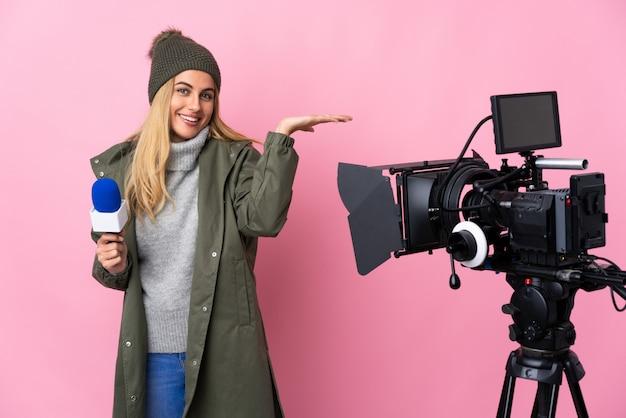 Repórter mulher segurando um microfone e reportando notícias sobre parede rosa segurando o espaço em branco imaginário na palma da mão