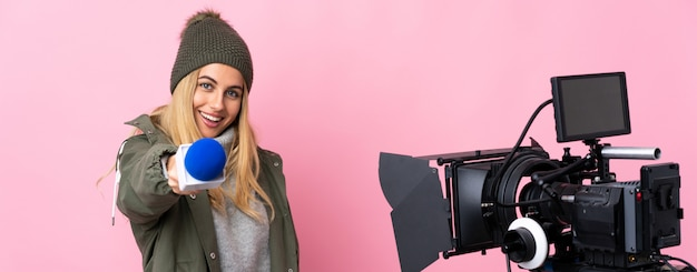 Repórter mulher segurando um microfone e reportando notícias sobre parede rosa