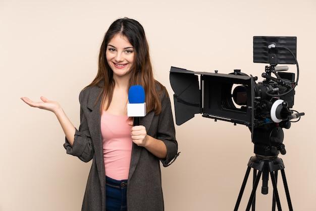 Repórter mulher segurando um microfone e reportando notícias sobre parede segurando espaço em branco imaginário na palma da mão