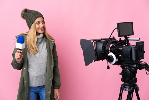 Repórter mulher segurando um microfone e reportando notícias sobre rosa isolado olhando para o lado e sorrindo