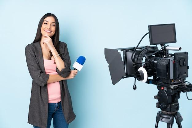 Repórter mulher segurando um microfone e reportar notícias isoladas na parede azul sorrindo