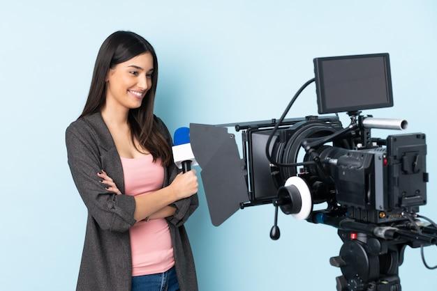 Repórter mulher segurando um microfone e reportar notícias isoladas na parede azul