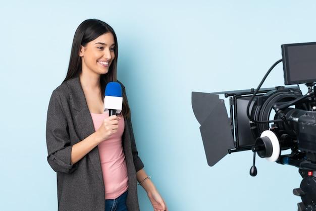 Repórter mulher segurando um microfone e reportar notícias na parede azul