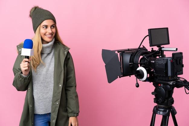 Repórter mulher segurando um microfone e reportar notícias sobre o lado olhando rosa isolado