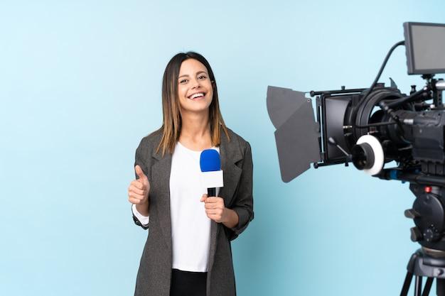 Repórter mulher segurando um microfone e reportar notícias sobre parede azul isolada, dando um polegar para cima gesto