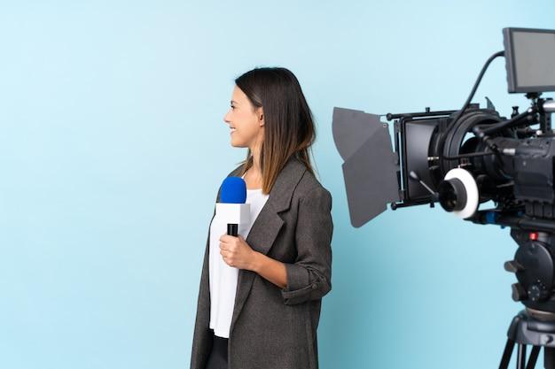 Repórter mulher segurando um microfone e reportar notícias sobre parede azul, olhando de lado