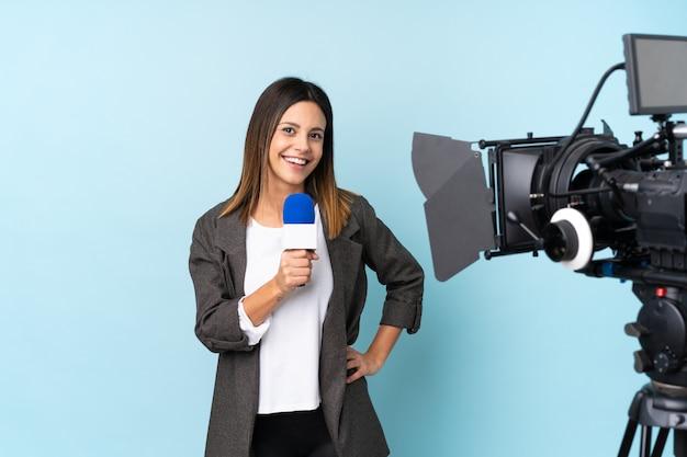 Repórter mulher segurando um microfone e reportar notícias sobre parede azul