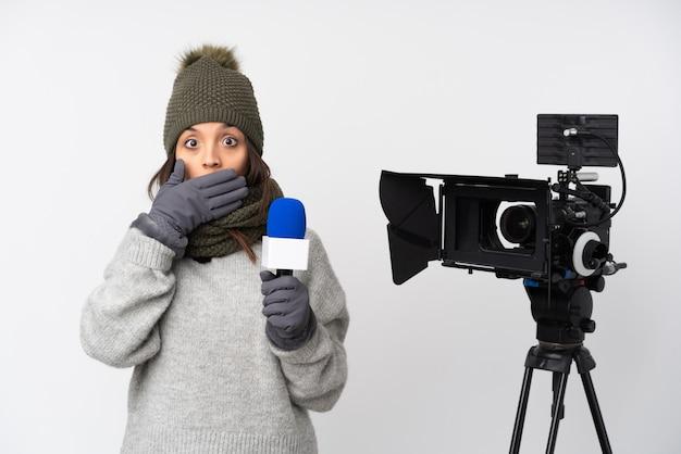 Repórter mulher segurando um microfone e reportar notícias sobre parede branca isolada, cobrindo a boca com as mãos