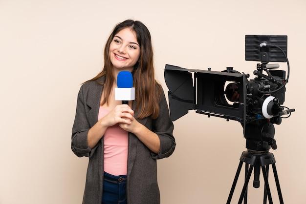Repórter mulher segurando um microfone e reportar notícias sobre parede rindo e olhando para cima