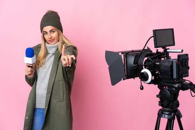 Repórter mulher segurando um microfone e reportar notícias sobre rosa isolado mostrando e levantando um dedo