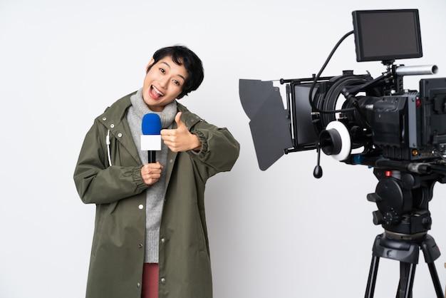 Repórter mulher vietnamita segurando um microfone e reportando notícias com polegares para cima porque algo bom aconteceu