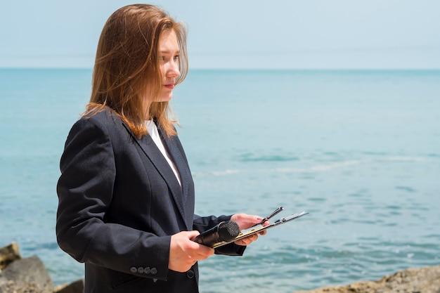 Repórter segurando o bloco de notas à beira-mar
