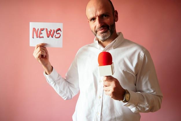 Repórter segurando um cartaz com a palavra noticiário escrita e um microfone na mão com fundo rosa