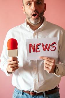 Repórter segurando um cartaz com a palavra noticiário escrita e um microfone na mão com uma parede rosa