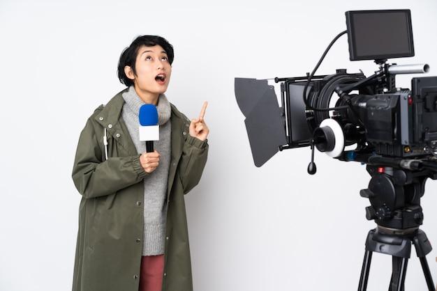 Repórter vietnamita mulher segurando um microfone e reportando notícias apontando para cima e surpreso