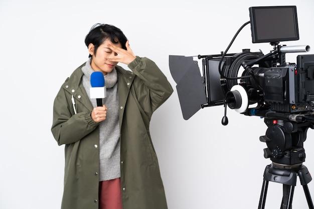 Repórter vietnamita mulher segurando um microfone e reportando notícias cobrindo os olhos pelas mãos e sorrindo