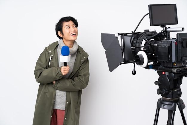 Repórter vietnamita mulher segurando um microfone e reportando notícias felizes e sorridentes