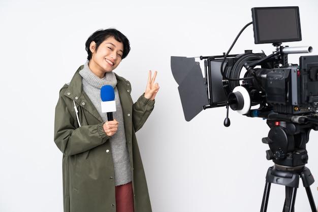 Repórter vietnamita mulher segurando um microfone e reportando notícias mostrando sinal de vitória com as duas mãos