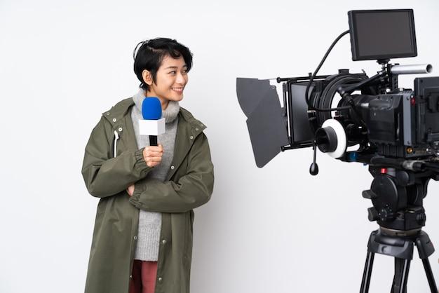 Repórter vietnamita mulher segurando um microfone e reportando notícias olhando de lado