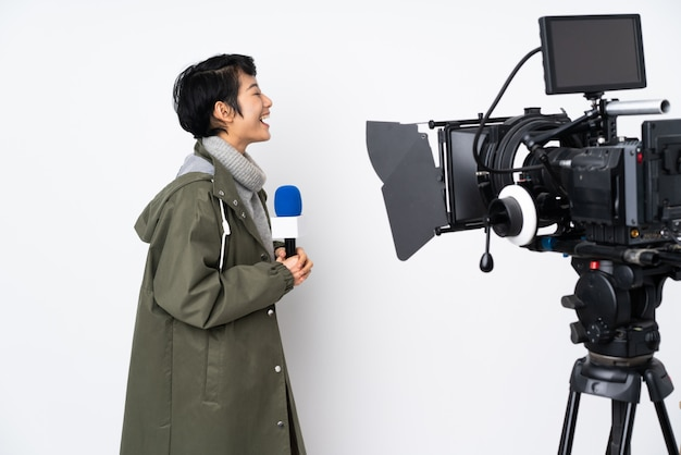 Repórter vietnamita mulher segurando um microfone e reportando notícias rindo na posição lateral