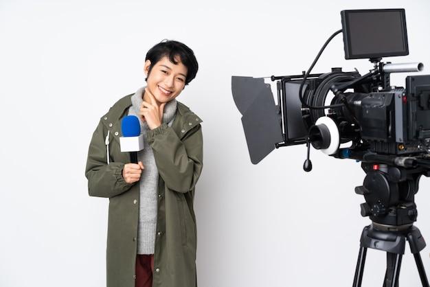 Repórter vietnamita mulher segurando um microfone e reportando notícias sorrindo