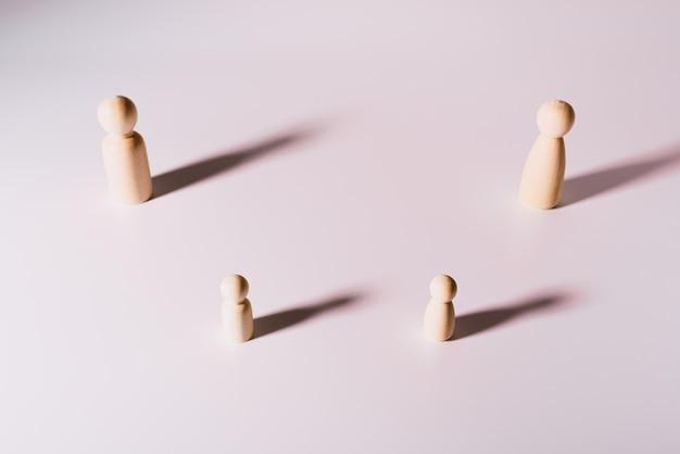 Representação de pessoas mantendo distância social, grupo de figuras de madeira no fundo branco