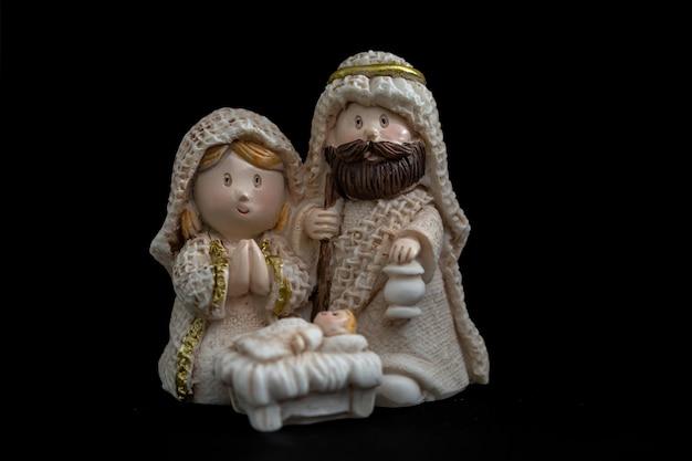 Representação de um presépio de natal com as pequenas figuras do menino jesus, maria e josé em fundo preto. conceito de natal.