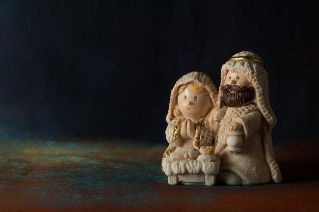 Representação de um presépio de natal com as pequenas figuras do menino jesus, maria e josé sobre um fundo de rocha.