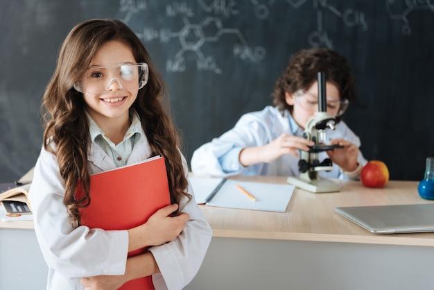 Representando nosso projeto de ciências. alunos felizes, alegres e capazes, de pé no laboratório e explorando a ciência enquanto trabalham no projeto e usam equipamentos