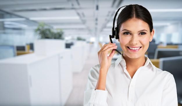 Representante de atendimento ao cliente, jovem sorridente falando pelo fone de ouvido