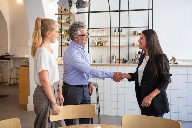 Representante de negócios feminina bem-sucedida em reunião com clientes e apertando as mãos