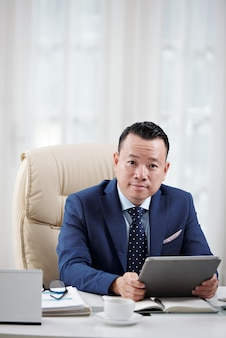 Representante de negócios sentado no escritório de luz com tablet digital