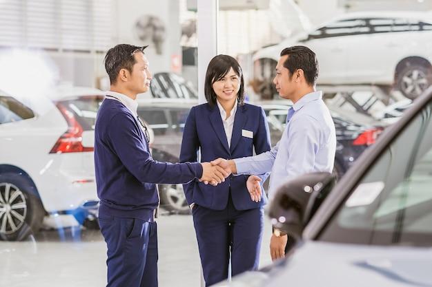 Representante de vendas asiática apresentando o serviço ao cliente. aperto de mão do líder mecânico