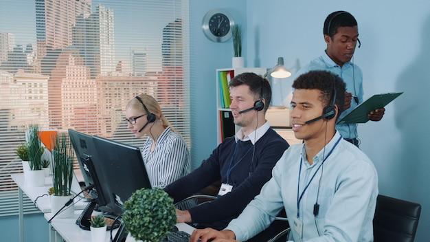 Representante multiétnico de atendimento ao cliente contando uma piada para seus colegas enquanto ligava para os clientes