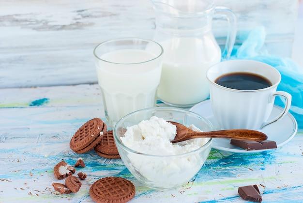 Requeijão e xícara de café preto em uma mesa de madeira