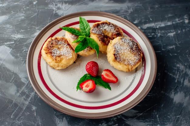Requeijão panquecas com morangos hortelã e açúcar de confeiteiro em um prato branco.