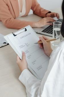 Requerente do sexo feminino, escrevendo suas informações pessoais e habilidades em formato de impressão na mesa do gerente de rh