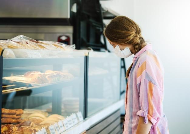 Requisito de máscara na padaria ou supermercado ao comprar pão devido a uma pandemia de alta qualidade.