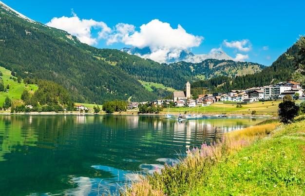 Reschen am see ou resia, uma vila no lago reschen no tirol do sul, alpes italianos