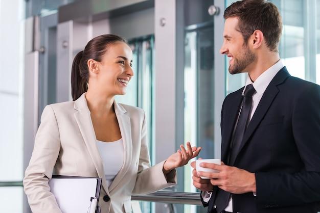 Reservando um tempo para conversar com o colega. dois alegres empresários discutindo algo e sorrindo