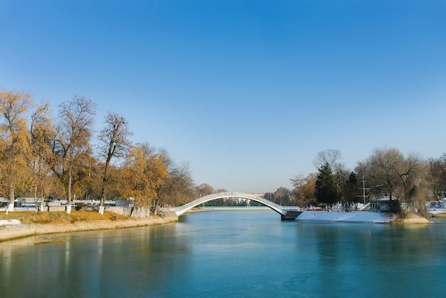 Reservatório no parque nacional do uzbequistão no inverno e uma ponte sobre o lago em um dia ensolarado