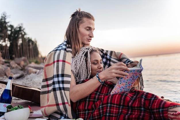 Reserve após o piquenique. casal adorável e fofo com mantas nos ombros se sentindo relaxado enquanto lê um livro após o piquenique
