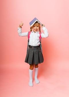 Reserve o teto sobre sua cabeça. menina segurando um livro na cabeça. menina lendo um livro infantil sobre um fundo rosa.