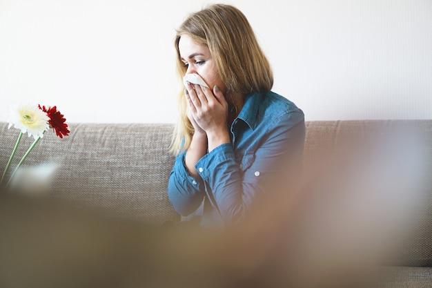 Resfriado de primavera ou alergias. uma jovem atraente é alérgica a flores, usa guardanapo em casa