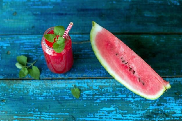 Resh suco de melancia com hortelã em uma jarra com um canudo em uma mesa de madeira azul