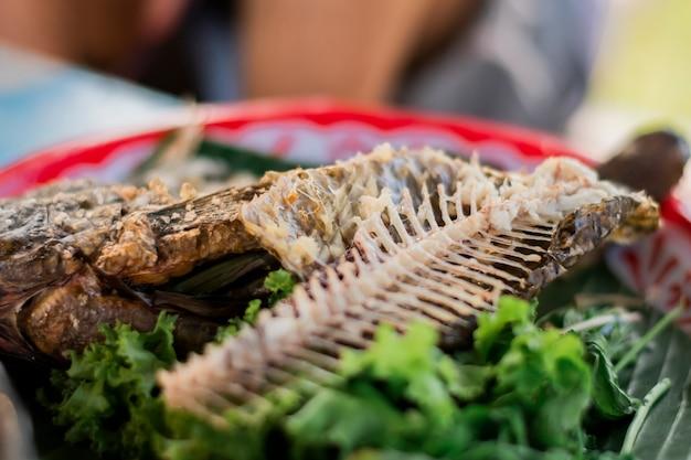 Resíduos de comida, restos de espinha de peixe, restos de vegetais na bandeja de comida