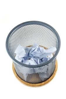 Resíduos de papéis e cesta isolados no branco.