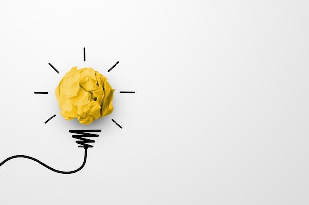 Resíduos de papel bola de cor amarela com o símbolo da lâmpada no fundo branco