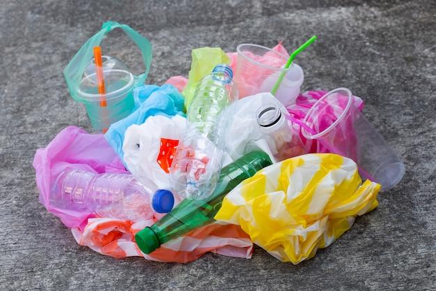 Resíduos de plástico colorido, sacos, copos, garrafas, palhas no chão de cimento